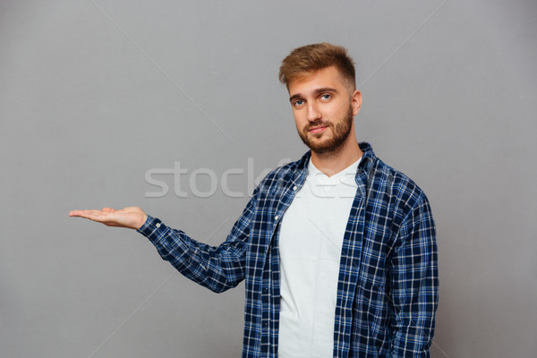 Happy smiling young man with beard holding copyspace on palm Stock photo © deandrobot