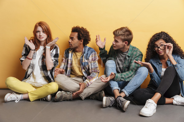 Multiethnic group of friends sitting and blaming unsure embarrassed girl Stock photo © deandrobot