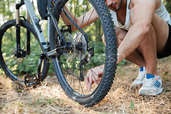 Man repairing mountain bike in the forest Stock photo © deandrobot