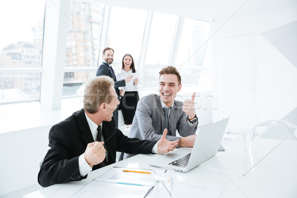 Stock photo: Side view Business partners by table with colleagues on background