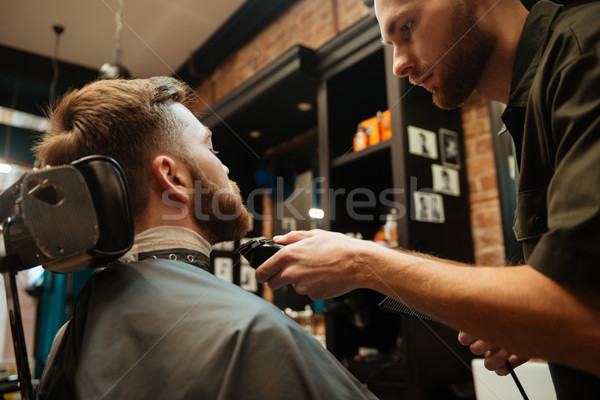 Man getting beard haircut by hairdresser while sitting in chair Stock photo © deandrobot