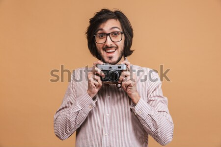 Happy hipster near the wall with retro camera Stock photo © deandrobot
