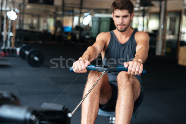 The young man is engaged in bodybuilding Stock photo © deandrobot