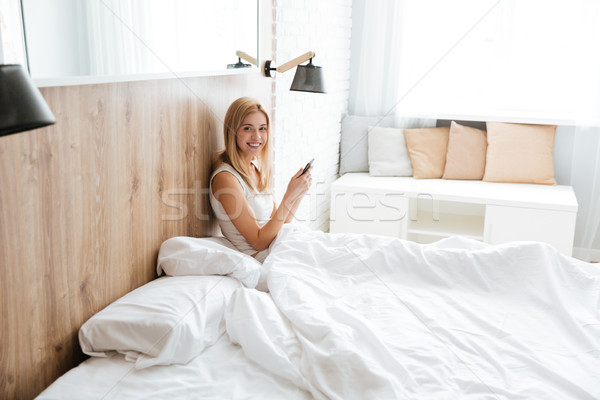 Side view of pretty woman lying on bed with phone Stock photo © deandrobot