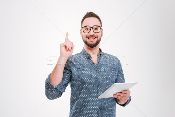 Happy bearded man holding tablet while have an idea Stock photo © deandrobot