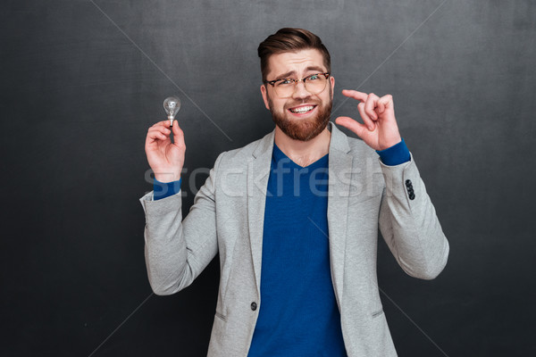 Cheerful young businessman holding light bulb and showing small size Stock photo © deandrobot