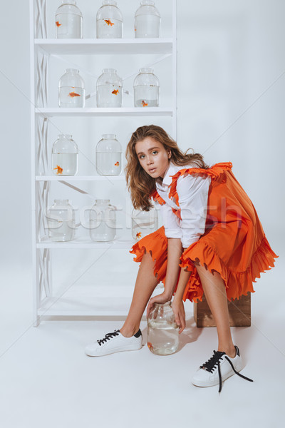 Lovely young woman with gold fish in glass jar Stock photo © deandrobot