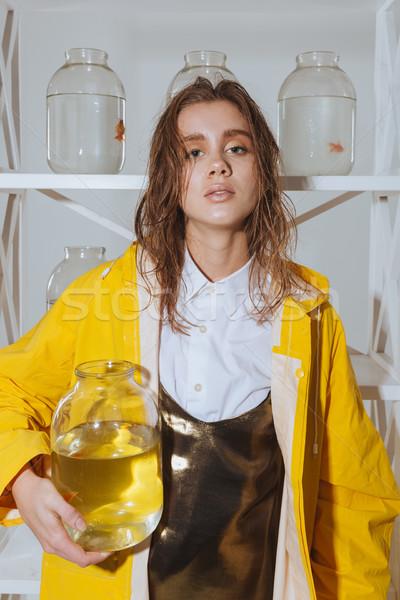 Bájos fiatal nő visel esőkabát arany hal Stock fotó © deandrobot