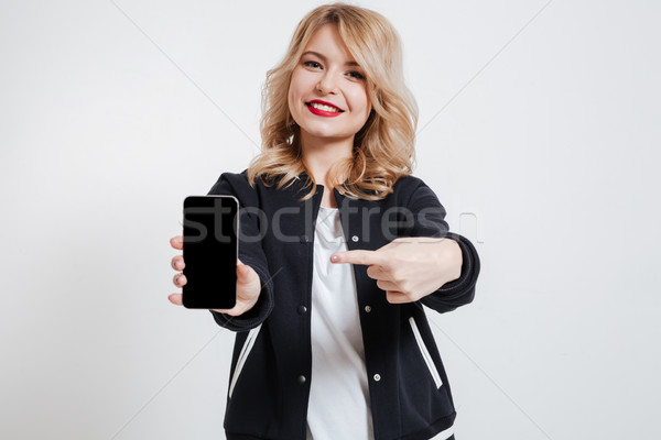 Happy young lady showing display of mobile phone and pointing. Stock photo © deandrobot