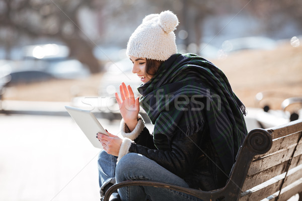 Cheerful woman having video conference using tablet outdoors Stock photo © deandrobot