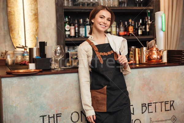 Smiling young woman standing in cafe. Stock photo © deandrobot