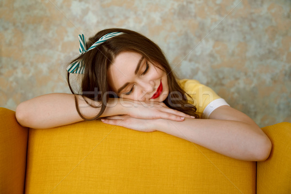 Young pretty pin up girl sleeping on a yellow chair Stock photo © deandrobot
