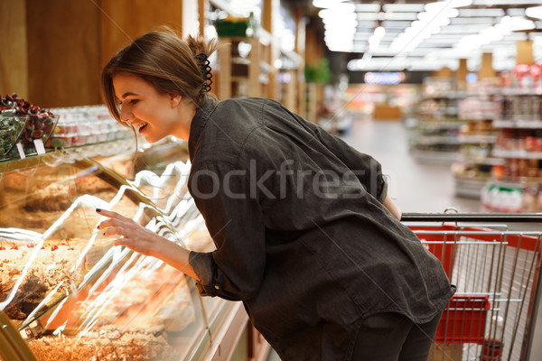 Smiling young lady standing in supermarket choosing pastries Stock photo © deandrobot