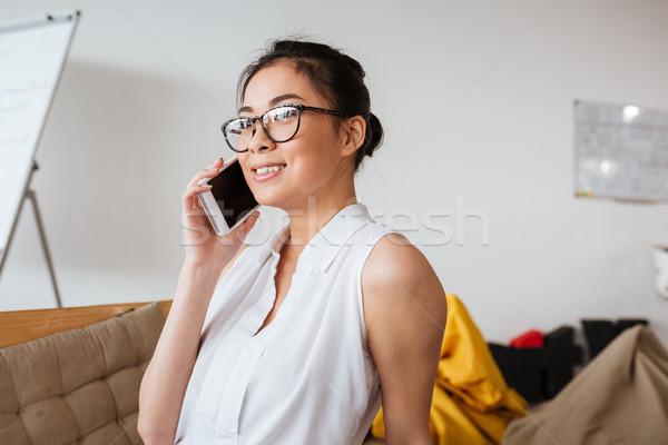 улыбаясь Cute сидят говорить сотового телефона Сток-фото © deandrobot