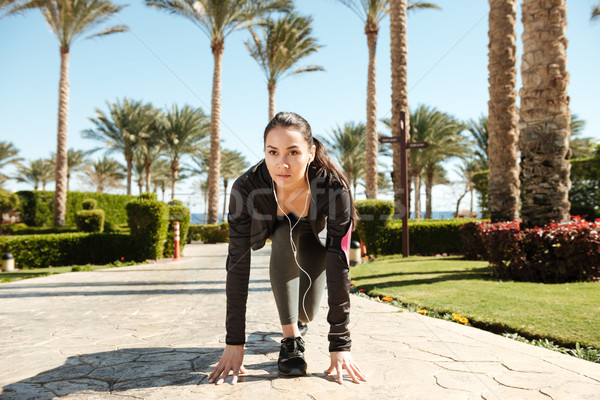Sportswoman with armband and earphones ready to run on resort Stock photo © deandrobot