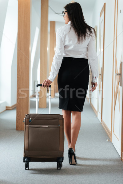 Woman in smart clothes walking along hotel lobby with suitcase Stock photo © deandrobot