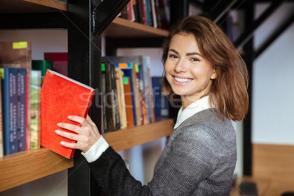 Młodych uśmiechnięta kobieta książki biblioteki półka Zdjęcia stock © deandrobot