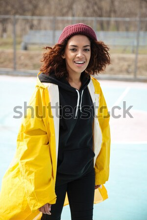 Pretty african curly young woman wearing yellow coat Stock photo © deandrobot