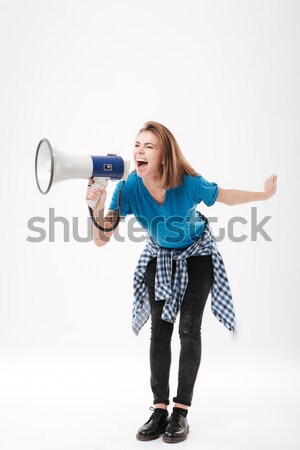 Screaming young pretty lady holding loudspeaker. Stock photo © deandrobot