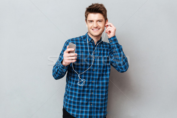 Pretty man looking camera while listening music Stock photo © deandrobot