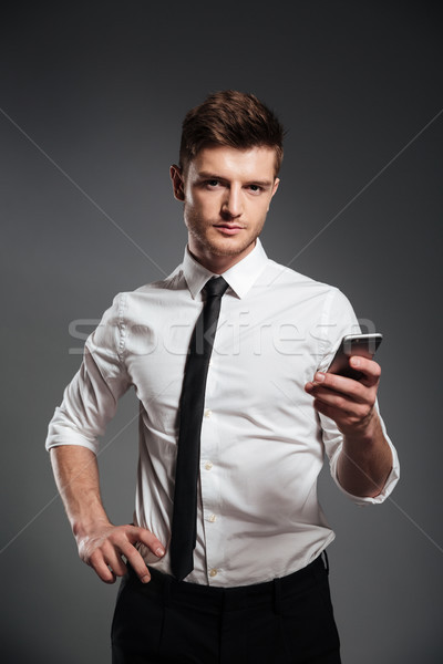 Businessman in formalwear holding mobile phone and looking at camera Stock photo © deandrobot