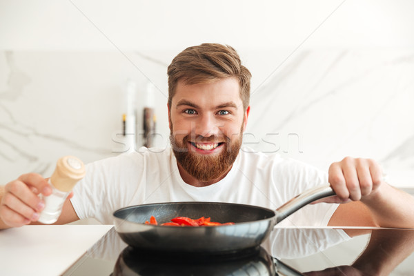 Smiling bearded man sprinkle with condiments of vegetables Stock photo © deandrobot