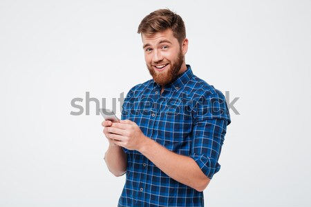 Surprised man in checkered shirt using smartphone Stock photo © deandrobot