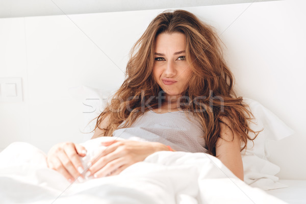 Displeased woman looking camera while lying in bed Stock photo © deandrobot