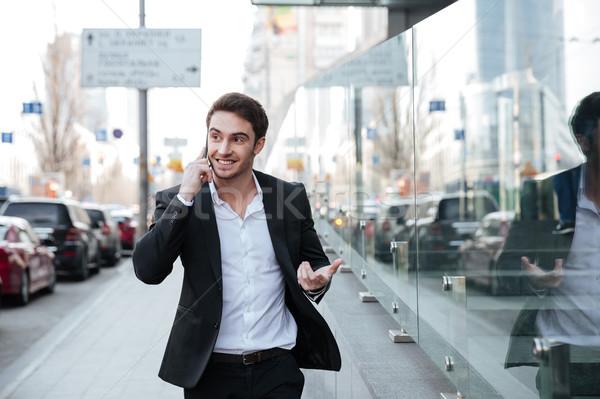 Derűs fiatal üzletember beszél telefon üzlet Stock fotó © deandrobot