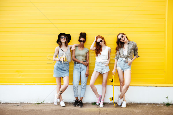 Stock photo: Young smiling women friends standing over yellow wall