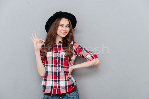 Positive girl in plaid shoort showing ok gesture and winking Stock photo © deandrobot