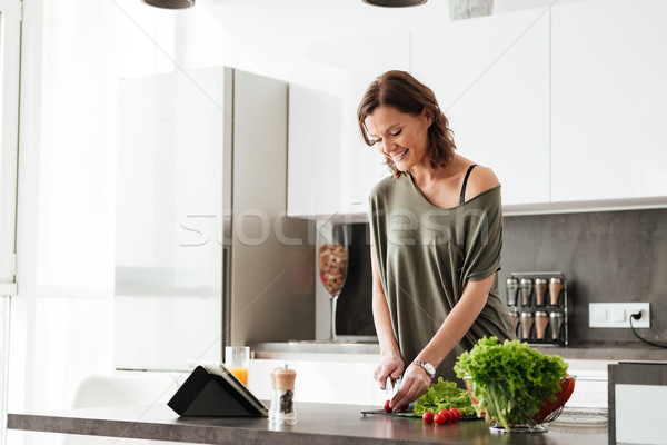 Smiling casual woman cuts vegetable by the table on kitchen Stock photo © deandrobot