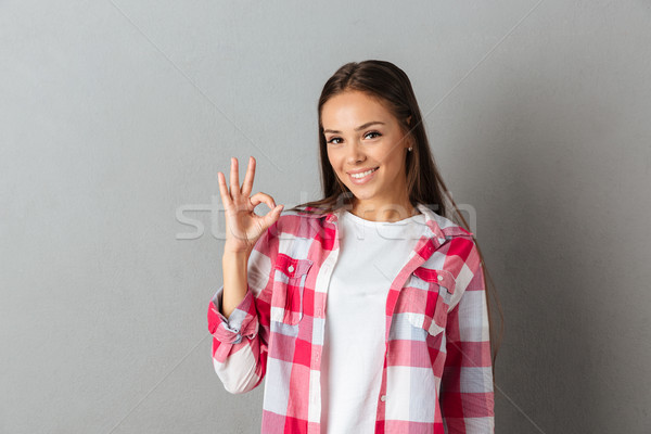 Close up photo of smiling young brunette woman in checkered shir Stock photo © deandrobot