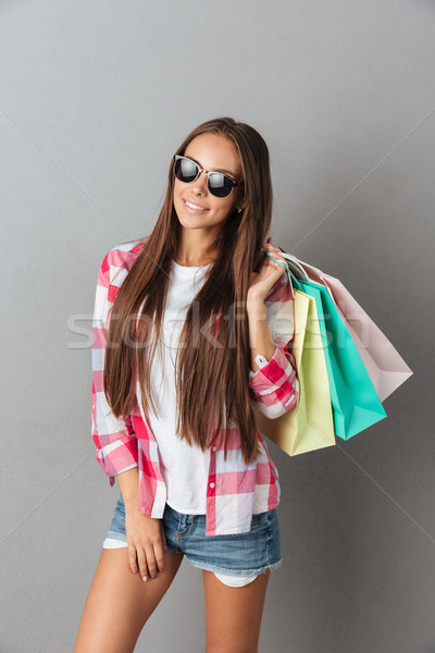 Portrait of young cheerful woman in glasses and casual wear, hol Stock photo © deandrobot
