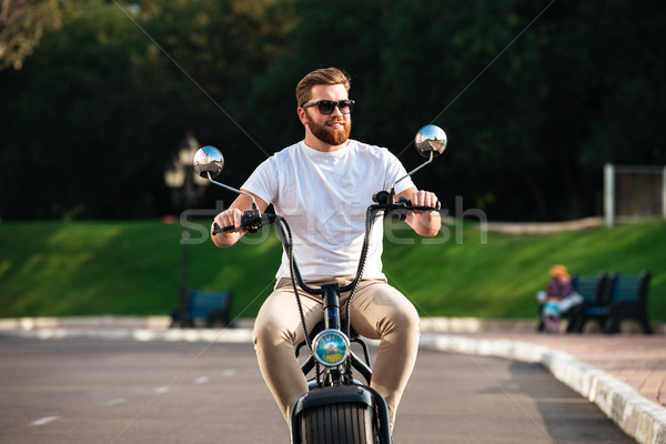 Smiling bearded man in sunglasses rides on modern motorbike Stock photo © deandrobot