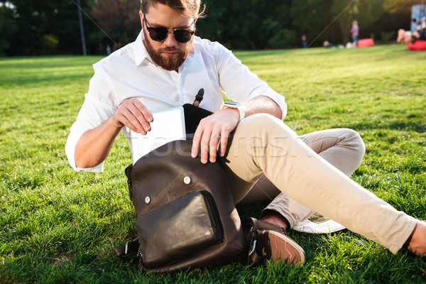 Serious bearded man sitting on grass outdoors getting tablet computer Stock photo © deandrobot