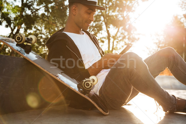 African young man surfing the web by using smartphone Stock photo © deandrobot