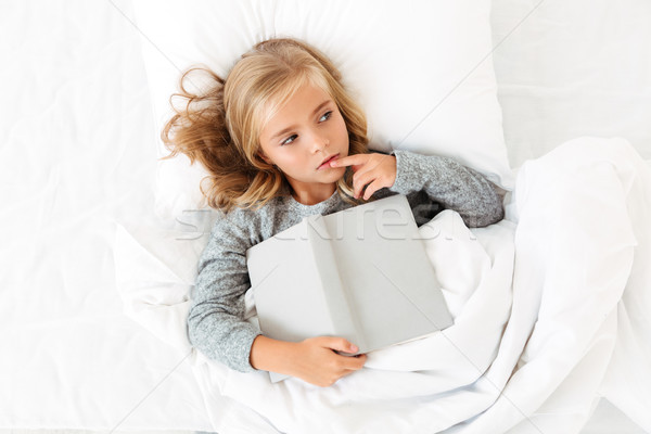 Top view photo of thoughtful little girl lying in bed with gray  Stock photo © deandrobot