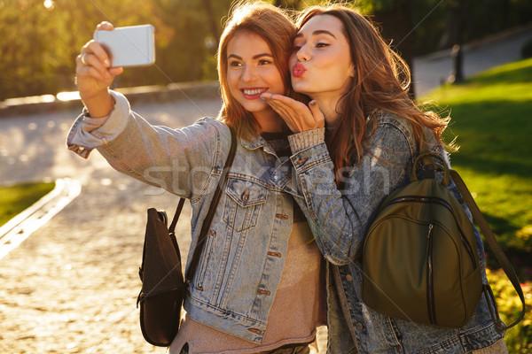 Two smiling female friends in casual wear making selfie on smart Stock photo © deandrobot