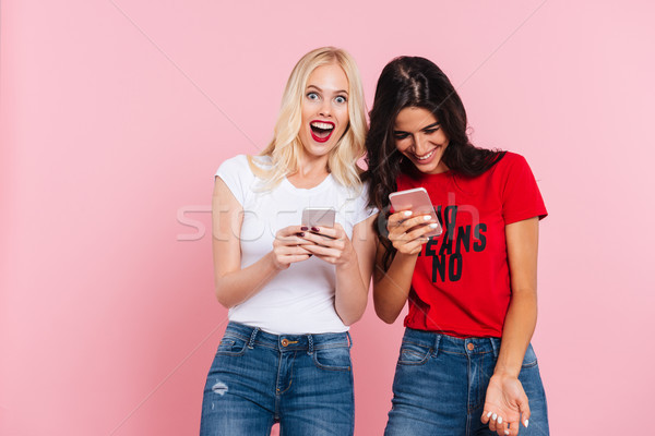 Laughing friends using smartphones and smiling isolated Stock photo © deandrobot