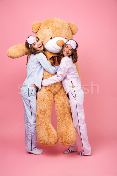 Cheerful friends women in pajamas hug big teddy toy bear Stock photo © deandrobot