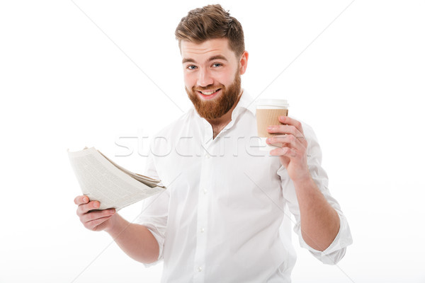 Pleased bearded man in business clothes holding newspaper Stock photo © deandrobot