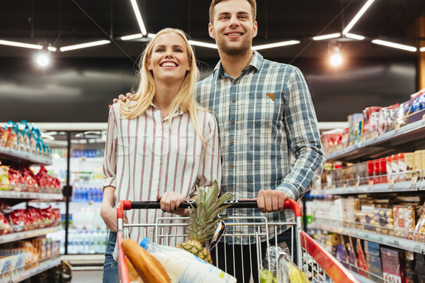 Stock photo: Cute couple grocery shopping together