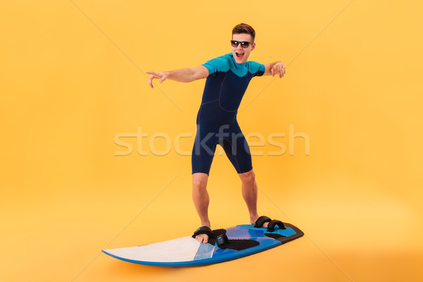 Image of happy surfer in wetsuit and sunglasses using surfboard Stock photo © deandrobot