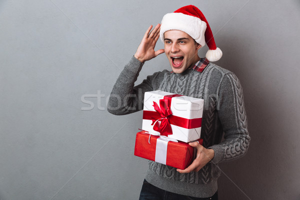 Pleased screaming man in sweater and christmas hat holding gifts Stock photo © deandrobot