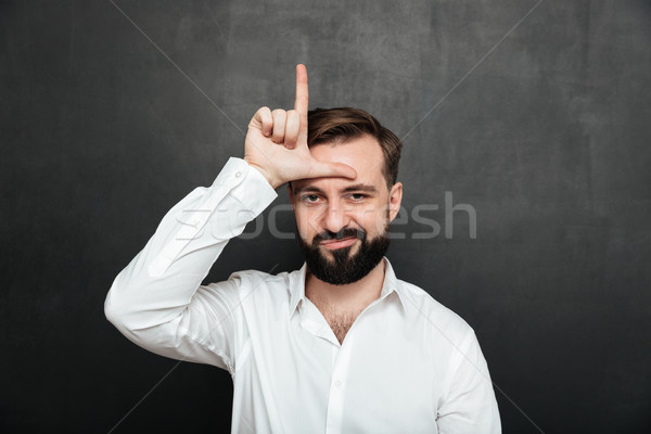 Portrait of unhappy guy 30s posing on camera and showing loser s Stock photo © deandrobot