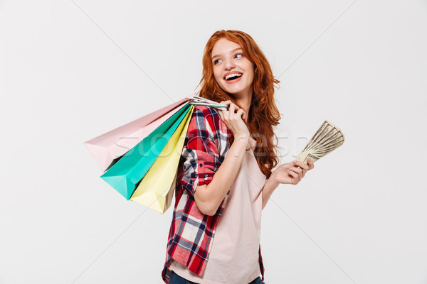 Pleased ginger woman in shirt holding packages on shoulder Stock photo © deandrobot