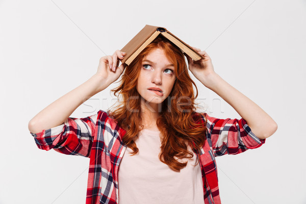 Ginger woman in shirt holding book on head like roof Stock photo © deandrobot