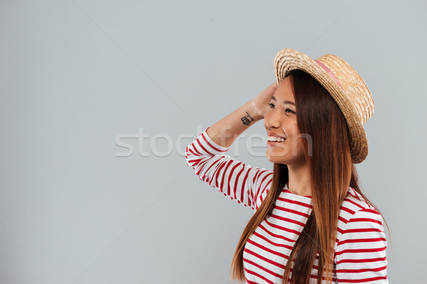 Pleased asian woman in sweater and hat looking away Stock photo © deandrobot