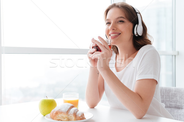 Cheerful young woman drinking tea listening music. Looking aside. Stock photo © deandrobot